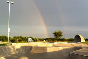 picture of a double rainbow in the sky behind the skatepark that people skate inside.