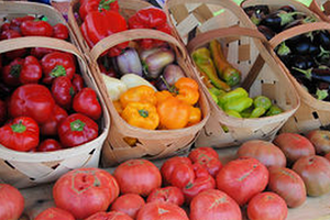 red, orange, and red peppers sitting inside of brown baskets